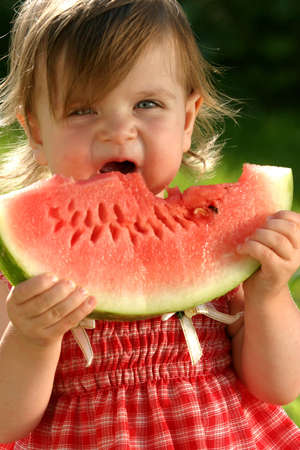 Little girl in red dress eating water-melon photo