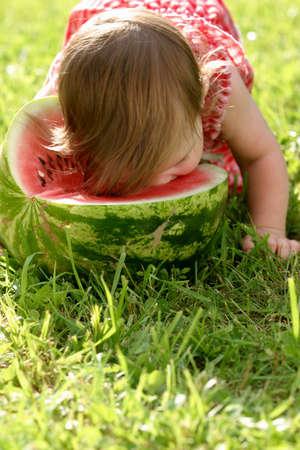 fruit eater: Little girl in red dress eating water-melon