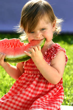 wondered: Little girl in red dress eating water-melon
