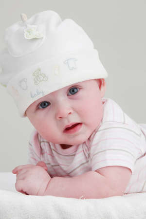 untruth: Baby in white looking to the camera Stock Photo