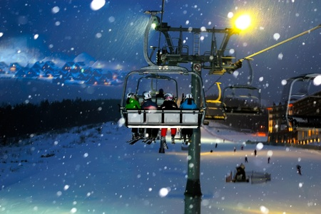downhill skiing: people ride in the chair lift, elevator, night landscape Stock Photo