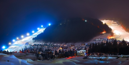 Winter ski resort at night in the mountains photo