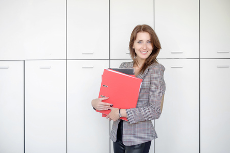 Beautiful business woman stands with a red folder in hands in a office