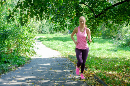 Beautiful young woman running in green park on sunny summer day Stock Photo