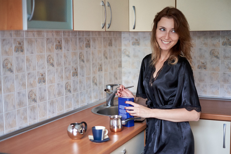 A picture of a young wife preparing coffee in the kitchen in the morning Stock Photo