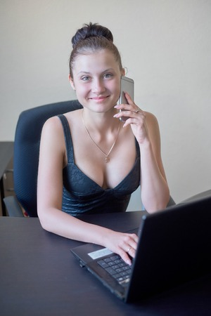 Beautiful and very sexy secretary working after hours at office and smile Stock Photo