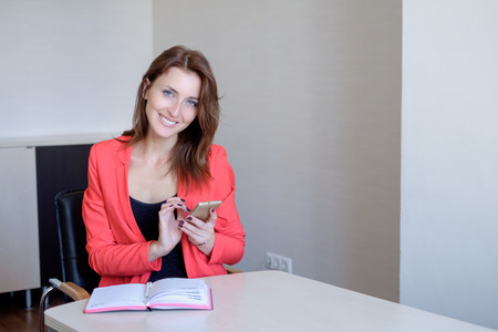 Secretary talking on mobile phone and writing notes while sitting at her desk. Stock Photo