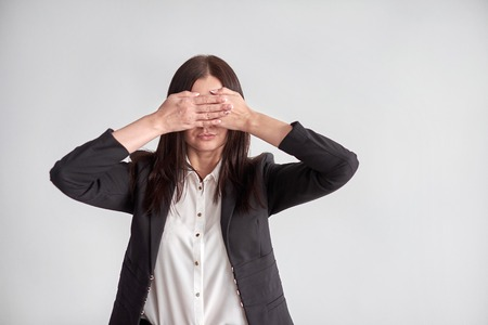 woman in a suit, blocking her eyes, business compliance concept