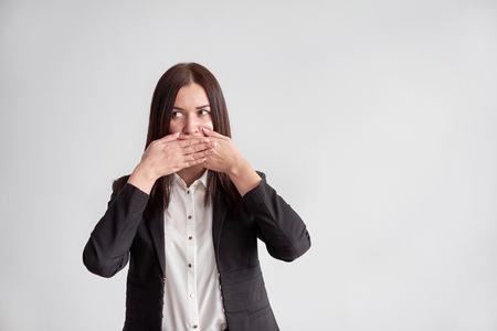 woman in a suit, blocking her mouth, business compliance concept
