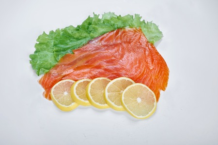 fillet of smoked red fish with lemon and herbs, isolated white background