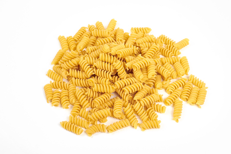 uncooked fusilli pasta noodles isolated on white background.