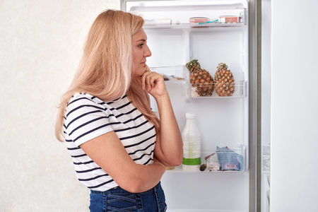 woman is standing in front of the fridge and thinks what to eat