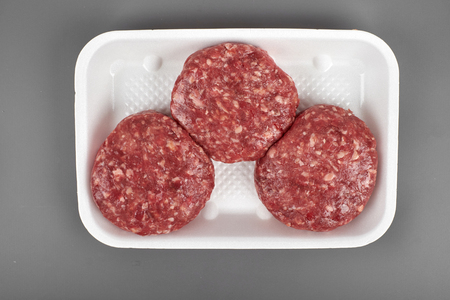 beef burgers in plastic package isolated on white background