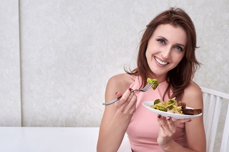 happy women is on dieting time looking at broccoli on the fork. concept healthy food Stock Photo