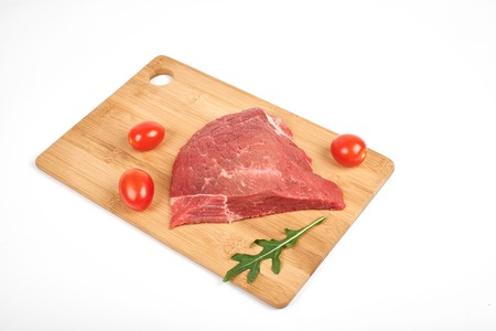 fresh raw beef on a cutting board isolated on white background