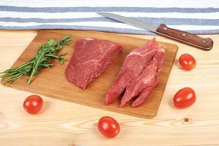 Sliced raw beef on cutting board and vegetables