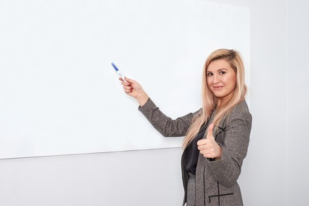 Portrait of young smiling businesswoman standing near flipchart in office and pointing on it Foto de archivo