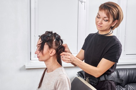 Professional hairdresser braiding clients hair Stock Photo