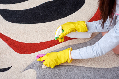 A picture of women hands in yellow gloves cleaning the floor