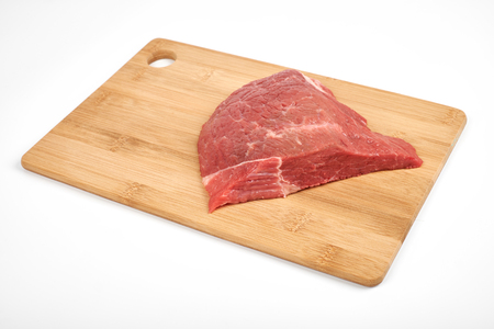 fresh raw beef on a cutting board isolated on white background.