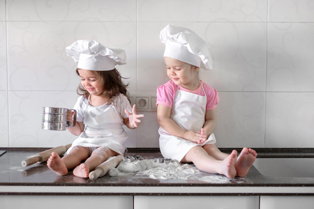 Two Little girl preparing cookies in kitchen at home