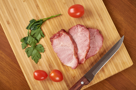 Cooked sliced pork barbecue steak on wooden cutting board