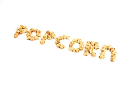 The word POPKORN is laid out from pieces of caramel popcorn on a white background. Standard-Bild - 110711584