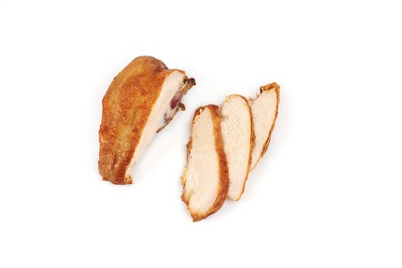 A close up of grilled, sliced chicken breast isolated on white background .