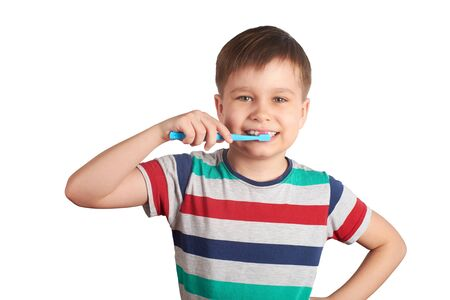 Smiling boy brushes his teeth, isolated on a white background