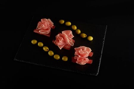 beautifully served prosciutto or jamon on a black slate board.