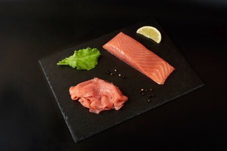 Sliced red fish fillet on the black shale board.
