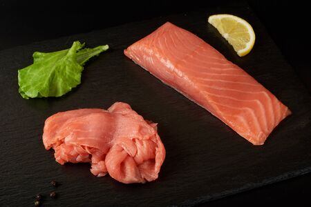 Sliced red fish fillet on the black shale board. Imagens - 149113929