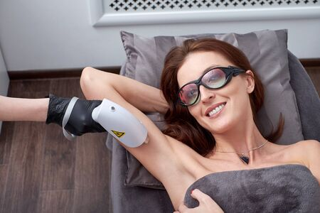 Woman doing cosmetology and lazer procedures. Laser hair removal, armpit hair removal. Woman in a laser hair removal salon