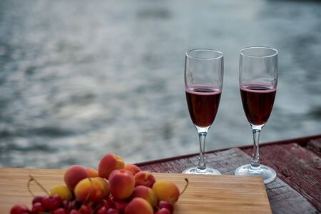 Two glasses of red wine, served outdoor with fruits and beautiful blue ocean view.