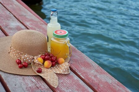 Glass of tropical exotic multifruit juice and fruits at the pier. Tropical beach picnic.