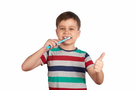 Smiling boy brushes his teeth and shows a thumbs up, isolated on a white background