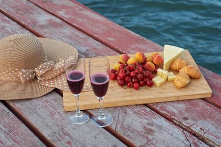Two glasses of red wine, served outdoor with fruits. Stok Fotoğraf