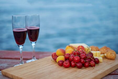 Two glasses of red wine, served outdoor with fruits and beautiful blue ocean view