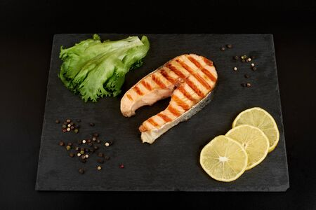 Grilled salmon steak with a lemon, tomatoes and salad on a slate plate. Imagens - 150114106