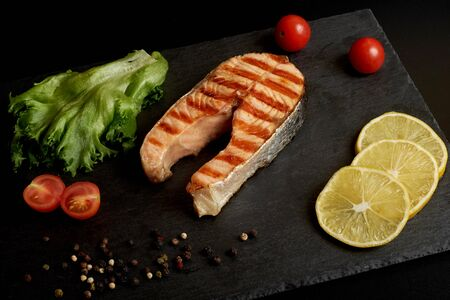 Grilled salmon steak with a lemon, tomatoes and salad on a slate plate. Stok Fotoğraf