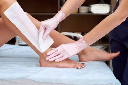 The process of female waxing. Beautician Waxing A Womans Leg Applying Wax Strip. Beautician removes wax with hair from female legs.