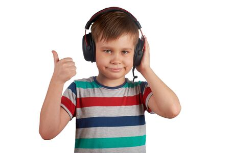 Kid listens to his favorite music on headphones and shows thumb up , isolated on white background. Leisure, music and entertainment concept. Stok Fotoğraf