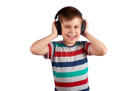 Child listens to his favorite music on headphones and dances to it , isolated on white background. Leisure, music and entertainment concept. Stok Fotoğraf
