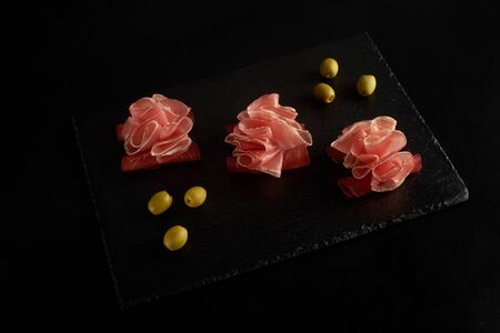 perfectly served prosciutto or jamon with olives on a black board.