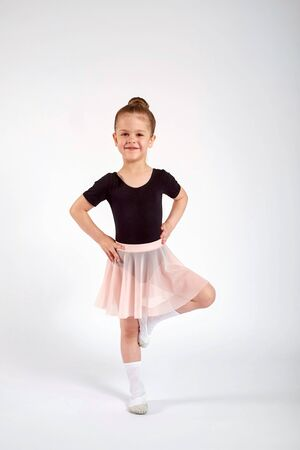 Little girl dressed in dance uniform is dancing over a white background in the studio.