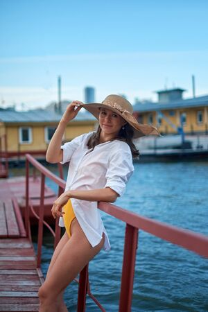 Beautiful girl in a hat , posing on a pier, on a background of water Imagens - 150114117