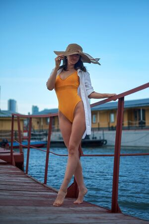 Beautiful girl in a hat , posing on a pier, on a background of water Imagens - 150114118