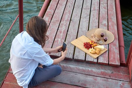 The girl beautifully served food on a pier and learns to photograph food. Photography training