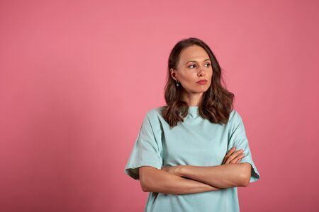 Portrait of a upset girl standing with arms folded over a pink background Stok Fotoğraf