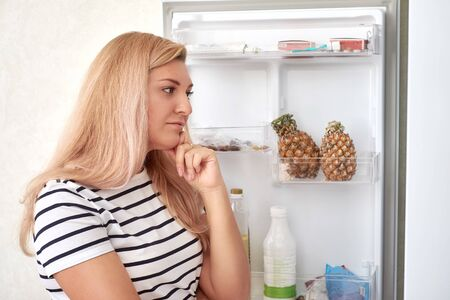 girl opened the refrigerator and thinks what to eat